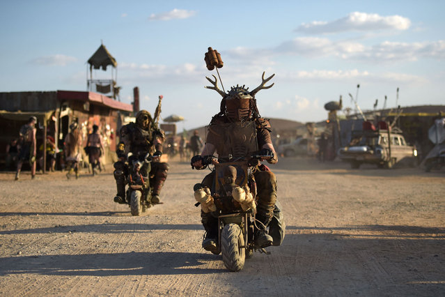 People attend Wasteland Weekend Festival at the Mojave desert in Edwards, California on September 25, 2021. The organizers require all festival goers to be in costume, with the idea of creating a full-inmersion effect, making attendees feel like theyre inside a Mad Max-style movie for 5 days. Activities include any number of themed distractions from the real world: live bands, DJs, car cruises, costume contests, a film festival, a post-apocalyptic swimsuit competition, Thunderdome battles, light-hearted role playing challenges like a bounty-hunting game, crafting workshops, free hair and makeup at the event-sponsored beauty salon, fire performers, a 24 hour radio station, post-apocalyptic gladiator fights, an archery range, a casino. (Photo by Agustin Paullier/AFP Photo)