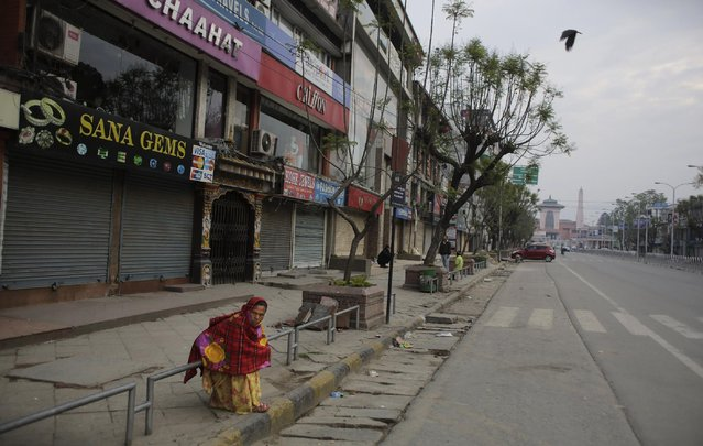 A Nepalese woman sits on a roadside in front of closed market in Kathmandu, Nepal, Tuesday, April 28, 2015. A strong earthquake shook Nepal's capital and the densely populated Kathmandu valley on Saturday. (Photo by Altaf Qadri/AP Photo)
