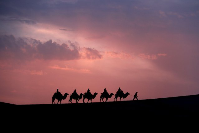 Tourists riding camels visit Mingsha Mountain and Crescent Spring scenic spot during Chinese National Day holiday on October 6, 2021 in Dunhuang, Gansu Province of China. (Photo by Zhang Xiaoliang/VCG via Getty Images)