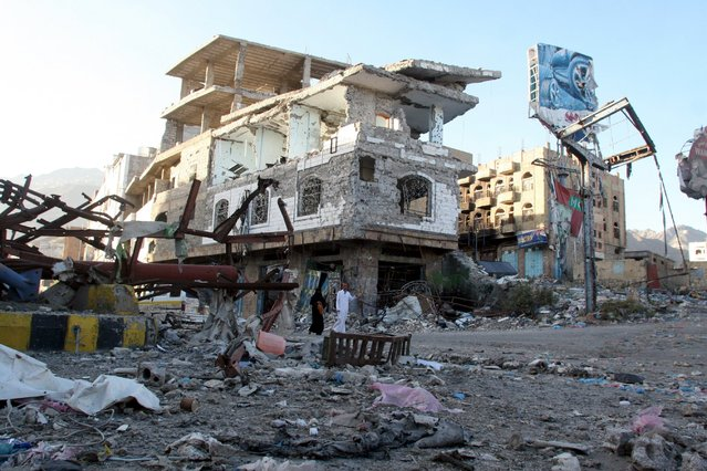 People walk past a building destroyed during recent fighting in Yemen's southwestern city of Taiz March 14, 2016. (Photo by Anees Mahyoub/Reuters)