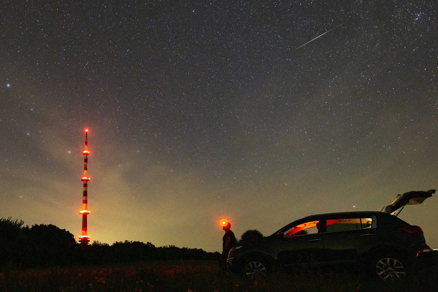 A meteorite of the swarm of meteorites Perseida flies above the Ujudvar TV Tower as seen from Ujudvar, Hungary, late Friday, August 13, 2021. Perseidas, one of the brightest meteorite swarms, consist of a multitude of stellar particles which due to their high speed glow up and burn by entering Earth's atmosphere. (Photo by Gyorgy Varga/MTI via AP Photo)
