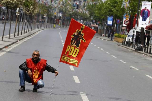 A demonstrator holds a flag as policemen block streets to prevent people from gathering for May Day demonstrations near Taksim Square in Istanbul, Turkey, May 1, 2015. (Photo by Umit Bektas/Reuters)