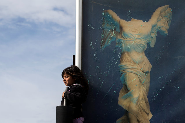 A girl stands on a disused airstair with a photo of the Victory of Samothrace, also called the Nike of Samothrace, during a protest of refugees and migrants, most of them Afghans, at the premises of the refugee camp at the old Hellenikon airport in Athens, Greece, February 6, 2017. (Photo by Alkis Konstantinidis/Reuters)