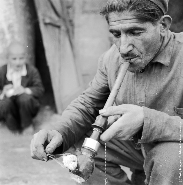circa 1950:  An Iranian smoking an opium pipe