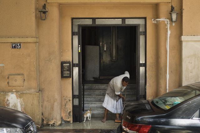 In this Friday, May 1, 2015 photo,  Salama Osman, a migrant from a southern village, cleans the entrance of his apartment building where he works in Cairo, Egypt. (Photo by Hiro Komae/AP Photo)