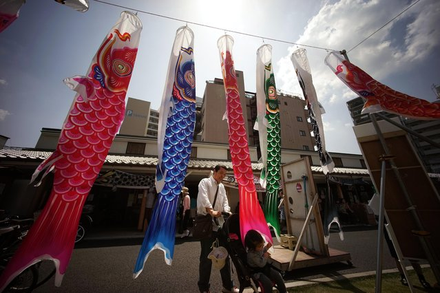 Carp streamers are hoisted in Tokyo, Saturday, May 2, 2015. The colorful streamers were hung to mark Children's Day on May 5, wishing children's healthy growth like carp that can swim up a waterfall. (Photo by Eugene Hoshiko/AP Photo)