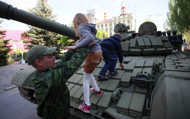 A pro-Russian rebel of the self-proclaimed Donetsk People's Republic helps children climb on a tank before rehearsals for the Victory Day parade in Donetsk on May 5, 2015. The Ukrainian army has been fighting pro-Russian militants for more than a year in the country's east in a conflict in which more than 6,100 have been killed. In February. (Photo by Aleksei Filippov/AFP Photo)