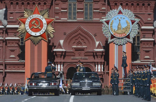 Russian Defence Minister Sergei Shoigu (standing in car at L) listens to Colonel-General Oleg Salyukov (second car, standing), Russia's Army Commander and Victory Parade Commander at the beginning of the Victory Day parade at Red Square in Moscow, Russia, May 9, 2015. (Photo by Reuters/Host Photo Agency/RIA Novosti)