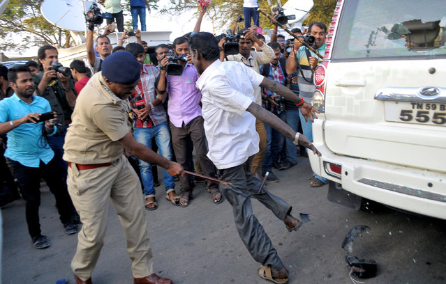 A policeman uses a baton to disperse the crowd as V. K. Sasikala (not pictured), general secretary of All India Anna Dravida Munnetra Kazhagam (AIADMK) and confidante of former Tamil Nadu Chief Minister Jayalalithaa Jayaram, arrives to surrender, outside the central jail in Bengaluru, India, February 15, 2017. (Photo by Abhishek N. Chinnappa/Reuters)