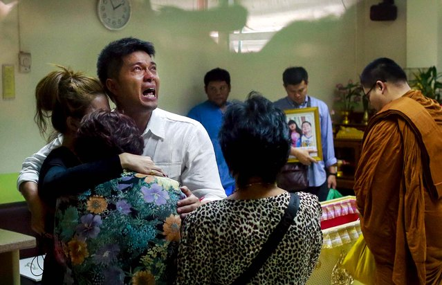 Tayakorn Yos-ubon, the father of two children killed in Sunday's bomb attack on an anti-government protest site, is embraced by his family as he breaks down during a ceremony at a hospital when he collects their bodies in Bangkok, Thailand, on February 24, 2014. Two young siblings, 6-year-old girl Patcharakorn and her 4-year-old brother Korawit, along with another woman were killed in an apparent grenade attack against anti-government protesters occupying an upscale shopping area of Thailand's capital day. (Photo by Wason Wanichakorn/Associated Press)