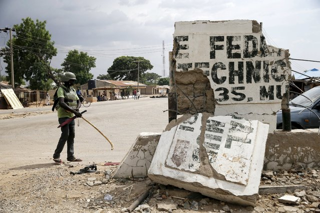 A local vigilante stands next to a broken signboard for the Federal Polytechnic at a junction in Mararaba, after the Nigerian military recaptures Michika and the surrounding towns from Boko Haram, Adamawa state May 10, 2015. (Photo by Akintunde Akinleye/Reuters)