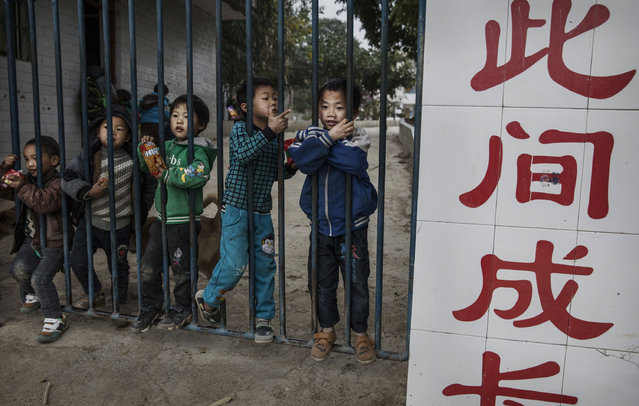 """""""Left behind"""" child Luo Lie,5, right, stands with friends at the gate to a local school on December 16, 2016 in Anshun, China. (Photo by Kevin Frayer/Getty Images)"""