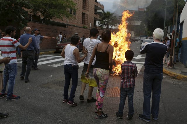 """People watch a burning effigy depicting Venezuela's President Nicolas Maduro during the traditional """"Burning of the Judas"""" as part of Easter celebrations in Caracas, March 27, 2016. (Photo by Marco Bello/Reuters)"""