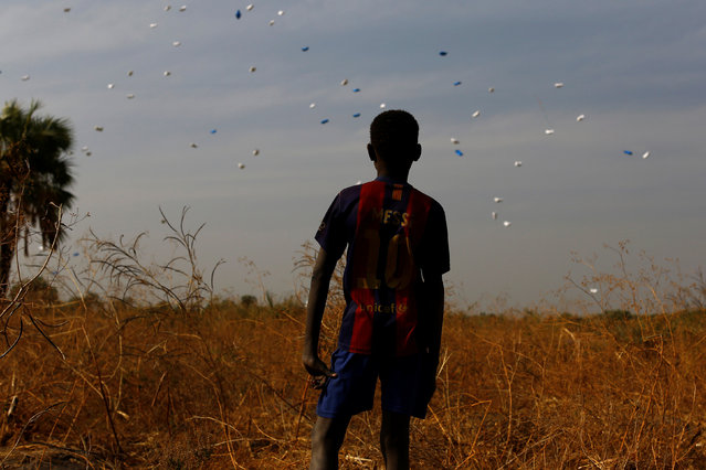 A boy watches sacks of food drop to the ground during a United Nations World Food Programme (WFP) airdrop close to Rubkuai village in Unity State, northern South Sudan, February 18, 2017. (Photo by Siegfried Modola/Reuters)