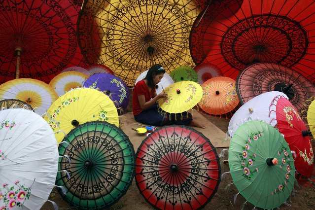 In this photo taken on May 17, 2015, a girl paints on an umbrella in Pathein township, Ayeyarwady Delta, Myanmar. (Photo by Khin Maung Win/AP Photo)