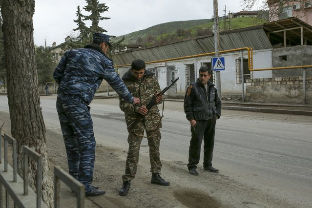 Ethnic Armenian fighters armed with a Kalashnikov machine gun stand at their positions on a road at Martakert province in the separatist region of Nagorno-Karabakh, Azerbaijan, Monday, April 4, 2016. (Photo by Vahan Stepanyan/PAN Photo via AP Photo)