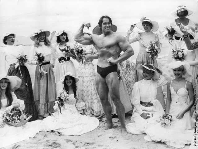 Arnold Schwarzenegger on Cannes beach during the Film Festival with the girls from the Folies Bergere, 1977