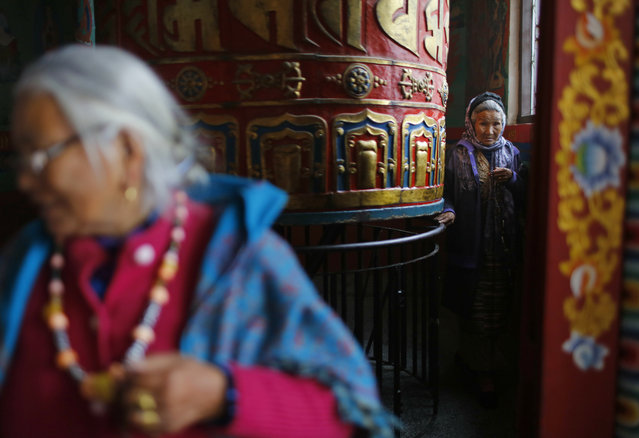In this Thursday, February 7, 2019, photo, an elderly Sherpa community woman spins prayer wheels on their New Year day New in Kathmandu, Nepal. Sherpa community members are welcoming the year of the pig. (Photo by Niranjan Shrestha/AP Photo)