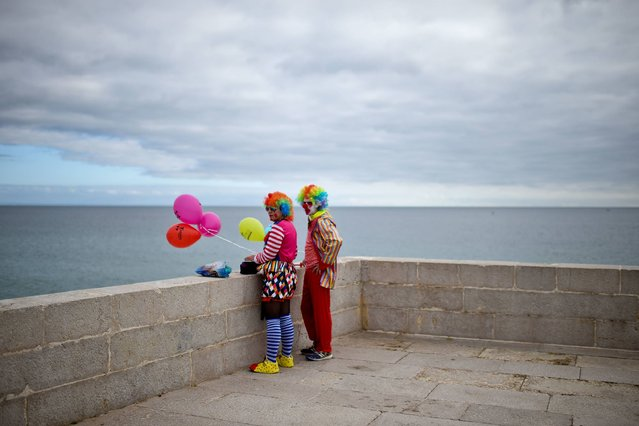 A couple dressed as clowns stands near the beach during the Carnival Clown's Parade at Sesimbra village, Portugal on February 27, 2017. (Photo by Patricia De Melo Moreira/AFP Photo)