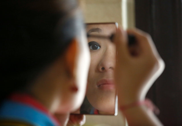 """A Tibetan girl in traditional attire looks into the mirror as she prepares ahead of a performance during a function organised to mark """"Losar"""", or the Tibetan New Year, in Kathmandu, Nepal March 1, 2017. (Photo by Navesh Chitrakar/Reuters)"""