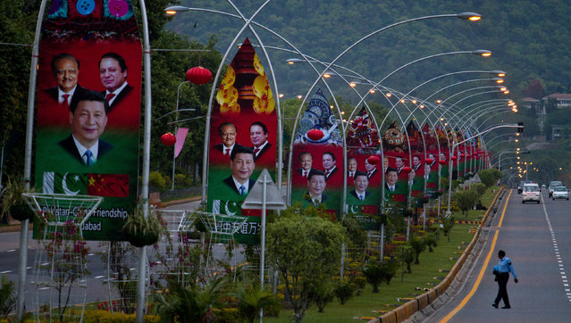 A Pakistani police officer walks pasts billboards showing pictures of Chinese President Xi Jinping, center, with Pakistan's President Mamnoon Hussain, left, and Prime Minister Nawaz Sharif welcoming Xi Jingping to Islamabad, Pakistan, Sunday, April 19, 2015. (Photo by Anjum Naveed/AP Photo)