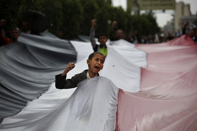 A boy chants slogans through a gap in a national flag raised by Shiite rebels, known as Houthis, during a protest against Saudi-led airstrikes in Sanaa, Yemen, Friday, April 15, 2016. (Photo by Hani Mohammed/AP Photo)