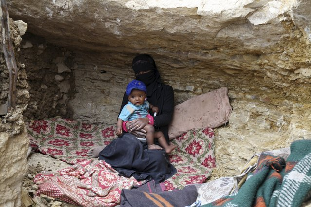 An internally displaced woman sits with a child in a cave in the district of Khamir of Yemen's northwestern province of Amran May 9, 2015. (Photo by Mohamed al-Sayaghi/Reuters)