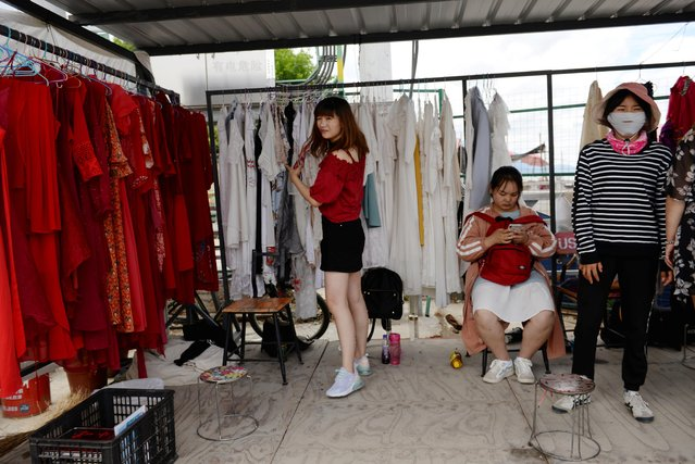 A woman selects outfits for photoshoots at a photo booth near Erhai Lake in Dali Bai Autonomous Prefecture, Yunnan province, China on June 15, 2019. (Photo by Tingshu Wang/Reuters)