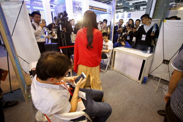 An exhibitor checks stock information on a mobile phone behind humanoid robot Jiajia produced by University of Science and Technology of China is displayed at an exhibition stage during the 4th China (Shanghai) International Technology Fair 2016 in Shanghai, China, April 21, 2016. (Photo by Aly Song/Reuters)