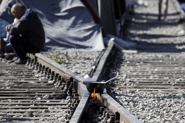 A pot over a bonfire was placed on the tracks of a railway station turned into a makeshift camp, crowded by migrants and refugees at the northern Greek border point of Idomeni, Greece, Monday, April 25, 2016. (Photo by Gregorio Borgia/AP Photo)