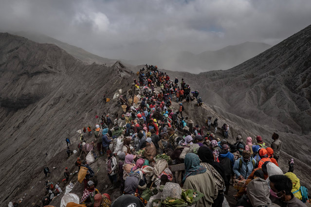 Tenggerese gather at crater of Mount Bromo during the Yadnya Kasada Festival on July 18, 2019 in Probolinggo, East Java, Indonesia. Tenggerese people are a Javanese ethnic group in Eastern Java who claimed to be the descendants of the Majapahit princes. Their population of roughly 500,000 is centered in the Bromo Tengger Semeru National Park in eastern Java. The most popular ceremony is the Kasada festival, which makes it the most visited tourist attraction in Indonesia. The festival is the main festival of the Tenggerese people and lasts about a month. On the fourteenth day, the Tenggerese made a journey to Mount Bromo to make offerings of rice, fruits, vegetables, flowers and livestock to throw them into the volcano's caldera. The origin of the festival lies in the 15th century princess named Roro, the principality of Tengger with her husband Joko Seger, and the childless couple asked mountain Gods for help in bearing children. The legend says the Gods granted them 24 children but on the provision that the 25th must be added to the volcano in sacrifice. The 25th child, Kesuma, was finally sacrificed in this initial after refusal, and the tradition of throwing sacrifices into the Caldera to appease the mountain Gods continues today. (Photo by Ulet Ifansasti/Getty Images)