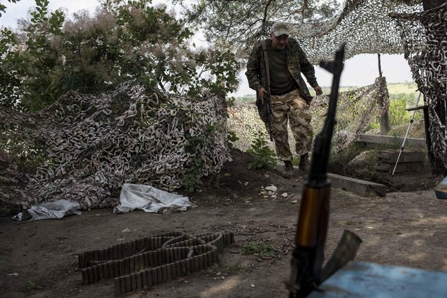 In this photo taken Tuesday, June 23, 2015 a Ukrainian serviceman from the Kiev-2 volunteer battalion guards his position at the frontline in the village of Krymske, east Ukraine. (Photo by Evgeniy Maloletka/AP Photo)