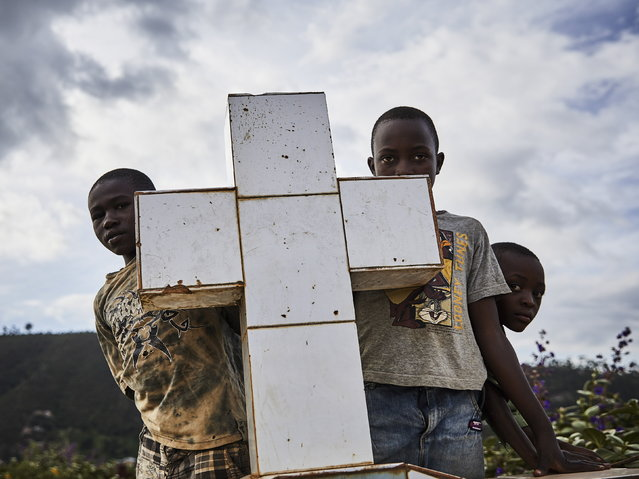 Local boys look at the funeral of Ebola victims, a fifty year-old woman Kavira Marie-Rosea and thirty two-year-old man Mumbi Bomboko, at Kitatumba cemetery in Butembo, North Kivu province, Democratic Republic of the Congo, 16 May 2019. Butembo is at the epicenter of Congo's Ebola crisis with multiple new cases, widespread community resistance to health workers and attacks carried out by the Mai Mai militia. (Photo by Hugh Kinsella Cunningham/EPA/EFE)