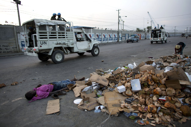 United Nations peacekeepers drive past a body lying amidst trash on the street, in central Port-au-Prince, Haiti, Sunday, June 28, 2015. (Photo by Rebecca Blackwell/AP Photo)