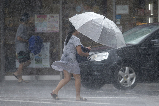 A Taiwanese woman makes her way against powerful gusts of wind generated by typhoon Lekima in Taipei, Taiwan, Friday, August 9, 2019. (Photo by Chiang Ying-ying/AP Photo)
