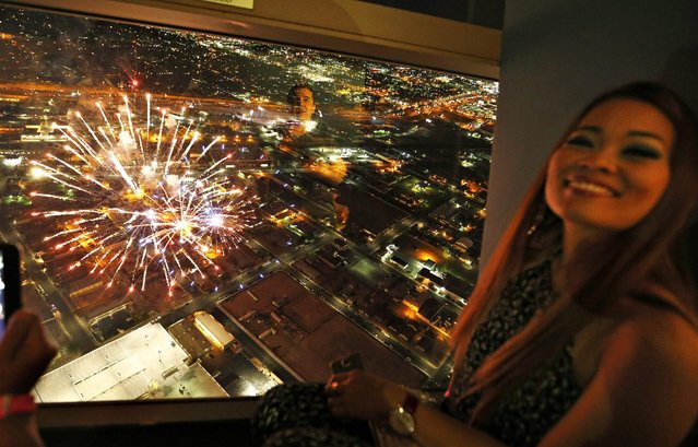 People watch Fourth of July fireworks from the Stratosphere hotel and casino Saturday, July 4, 2015, in Las Vegas. (Photo by John Locher/AP Photo)