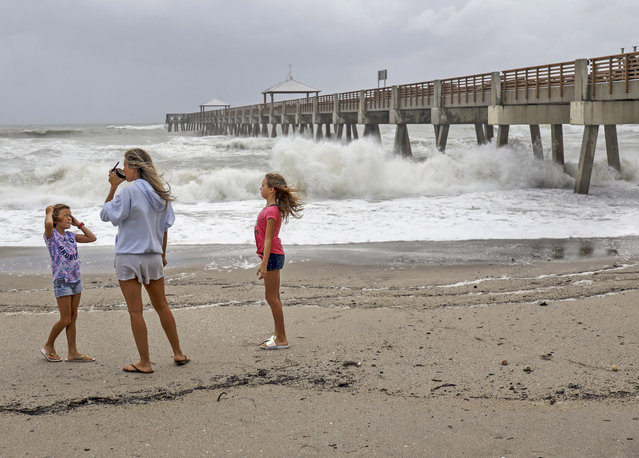 Juna Beach residents Anneka, 8, left, and sister, Breanna, 10, right, along with their mother, Leah Hanza, center, get a close look of the waves crashing against the Juno Beach Pier as Hurricane Dorian crawls toward Florida, and it continues to ravage the Bahamas on Monday, September 2, 2019. (Photo by Carl Juste/Miami Herald via AP Photo)