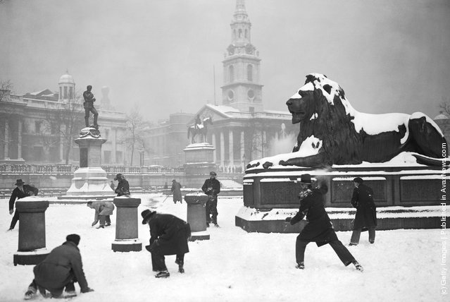 1931: A group of gents enjoy an impromptu snowball fight in the serene and stately setting of a still and snow covered Trafalgar Square, London