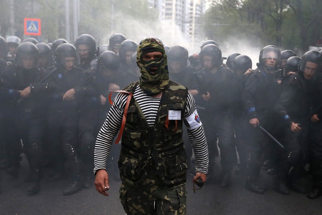 A pro-Russian protester walks in front of riot police during a pro-Ukraine rally in the eastern city of Donetsk April 28, 2014. Several people were wounded when what appeared to be stun grenades exploded during a rally in support of Ukrainian unity in the eastern, separatist-held city of Donetsk on Monday, a Reuters reporter said. (Photo by Marko Djurica/Reuters)