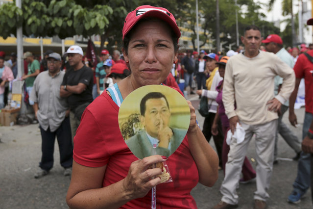 A government supporter holds an image of Venezuela's late president Hugo Chavez, during a march in Caracas, Venezuela, Wednesday, April 19, 2017. (Photo by Fernando Llano/AP Photo)