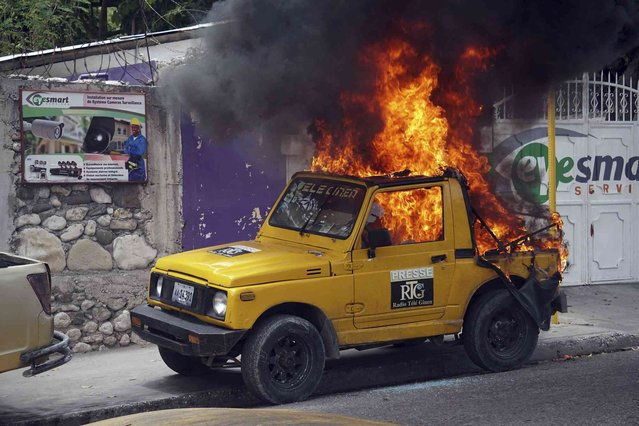 A car that belongs to Radio Tele-Ginen burns during a protest demanding the resignation of President Jovenel Moise in Port-au-Prince, Haiti, Monday, June 10, 2019. Opposition leaders in Haiti launched a two-day strike that paralyzed the country's capital amid another day of protests demanding that President Jovenel Moise resign over corruption allegations. (Photo by Edris Fortune/AP Photo)
