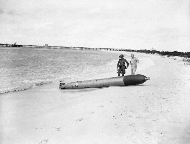 A torpedo fired by an Axis submarine in its attack on tankers off Aruba Dutch West Indies, is inspected by Dutch, left, and U.S. Army officers after it washed up on the beach unexploded, February 16, 1942. The 18-F missile went off, killing four Dutchmen who were trying to take it apart. The Americans is officer, Capt. Robert Bruskin, former Washington and Baltimore newspaperman. (Photo by AP Photo)