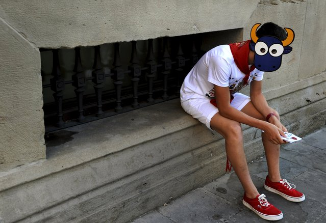 """A boy wears a bull mask on the eighth day of the San Fermin festival in Pamplona, northern Spain, July 13, 2015. The festival, a heady mix of drinking, dancing, late nights and bullfights, made famous by Ernest Hemingway in his novel """"The Sun Also Rises"""", runs for nine days until July 14. (Photo by Eloy Alonso/Reuters)"""