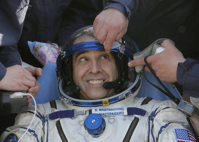 U.S. astronaut Rick Mastracchio is helped by medical staff and technicians shortly after the landing of the Russian Soyuz TMA-11 space capsule, south-east of the town Dzhezkazgan,  Kazakhstan, May 14, 2014. A Soyuz space capsule with Japanese astronaut Koichi Wakata, Russian cosmonaut Mikhail Tyurin and U.S. astronaut Rick Mastracchio, returning from a five-month mission to the International Space Station, landed safely Wednesday on the steppes of Kazakhstan. (Photo by Dmitry Lovetsky/Reuters)