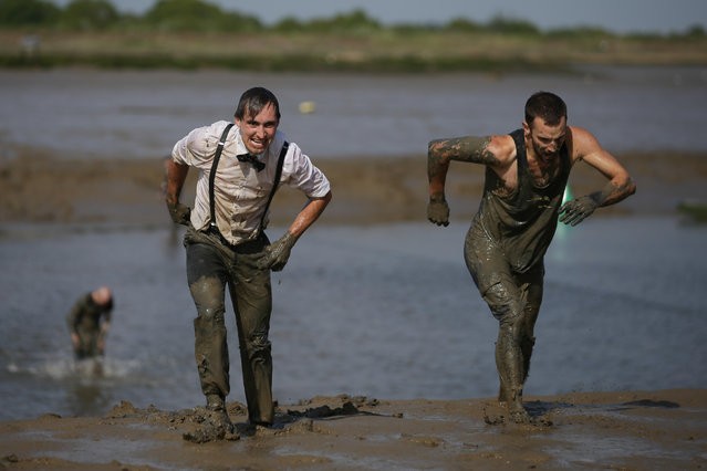 Participants arrive at the finish line of the annual Maldon Mud Race in Maldon, east England on May 7, 2017. (Photo by Daniel Leal-Olivas/AFP Photo)