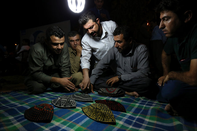 In this Tuesday, July 7, 2015 photo, Kurdish men discuss which hat to pick up while playing a game of Klawane in Irbil, Iraq. The traditional Iraqi Kurdish game is only played after Iftar during Ramadan. Two teams of four compete, where one team hides a ring in a traditional hat. The other team has to guess in which hat the ring is hidden. The team that hides the ring scores points for each hat that is leftover after the other team finds the ring. (Photo by Bram Janssen/AP Photo)