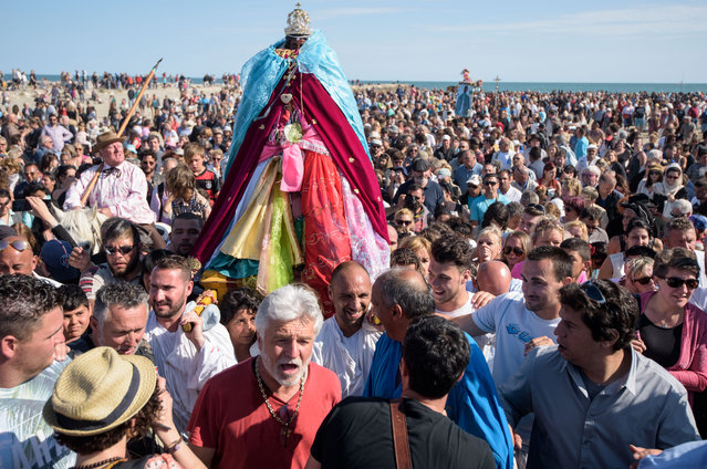"""Gypsies carry the sculpture of """"Sara the Black"""" to the sea after a church service and a procession on May 24, 2016 in Staintes Maries de la Mere near Arles, France. (Photo by Thomas Lohnes/Getty Images)"""
