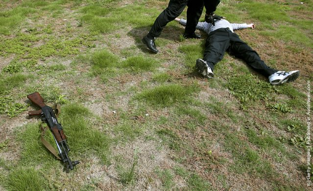 A policeman inspects a simulated suspect who has been shot down during an anti-terror drill