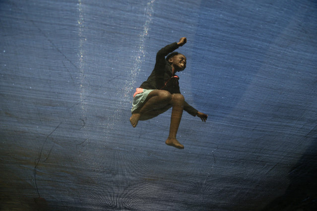 Twelve year-old girl Simphiwe Gama enjoys jumping on a trampoline in Katlehong, about 30Km east of Johannesburg, South Africa, Monday, July 13, 2015. The trampoline is set up by a resident and operated for the local community, charging 50 cents for five minutes of jumping fun. (Photo by Themba Hadebe/AP Photo)