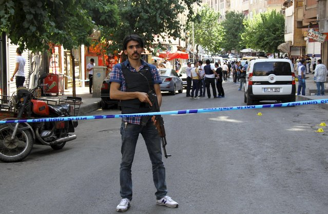 A plainclothes policeman stands guard following an attack on police officers in Diyarbakir, Turkey, July 23, 2015. A Turkish police officer was shot and killed and a second wounded on Thursday in the mainly Kurdish city of Diyarbakir in the latest in a series of attacks that began with a suicide bombing blamed on Islamic State, security sources said. T(Photo by Sertac Kayar/Reuters)